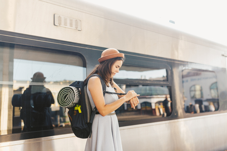 Theme transportation and travel. young Caucasian woman with toothy smile standing at station train background with backpack waving checks time on wrist hand wrist watch in dress and hat in summer.