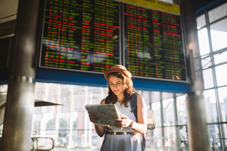 theme travel and transportation. Beautiful young caucasian woman in dress and backpack standing inside train station terminal looking at electronic scoreboard holding phone, map paper hand navigation.