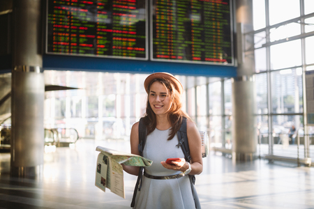 theme travel and transportation. Beautiful young caucasian woman in dress and backpack standing inside train station terminal looking at electronic scoreboard holding phone, map paper hand navigation. Standard-Bild - 115334599