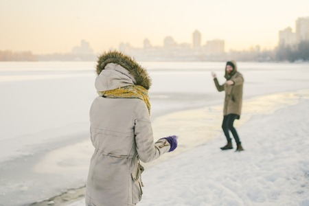 Young Caucasian people in love heterosexual couple have a date in winter near a frozen lake. Active holiday holiday Valentine's Day, playing snowballs and playing joy. Stock Photo