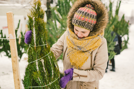 Theme is the symbol of Christmas and New Year holidays. Beautiful young Caucasian female shopper, chooses, makes a purchase at the Christmas tree market in the winter outside in snowy weather.