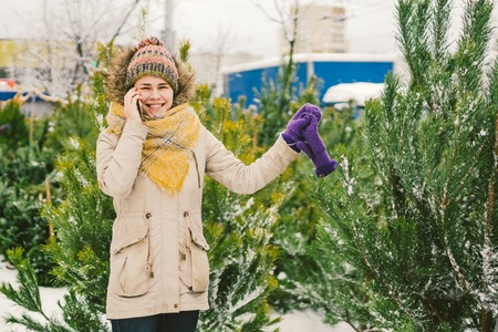 Theme is symbol of Christmas and New Year holidays. Beautiful young Caucasian woman with phone. Hand buyer chooses, makes purchase on Christmas tree market in winter outside in snowy weather.