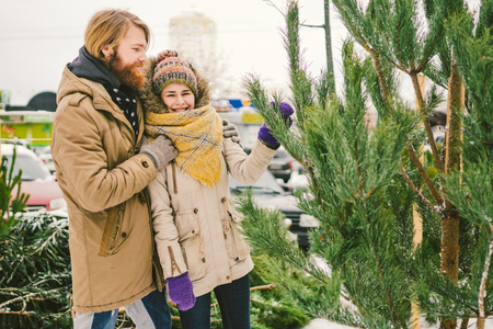 Theme is the symbol of Christmas and New Year holidays. Beautiful young Caucasian heterosexual couple buyer chooses, makes a purchase on the Christmas tree market in winter outside in snowy weather. Stock Photo