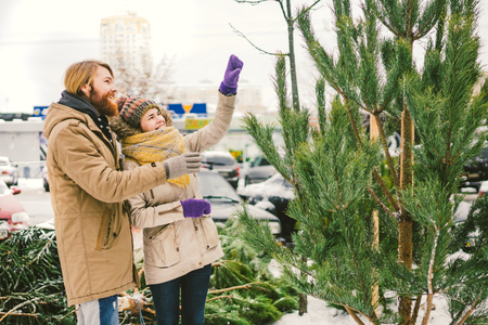 Theme is the symbol of Christmas and New Year holidays. Beautiful young Caucasian heterosexual couple buyer chooses, makes a purchase on the Christmas tree market in winter outside in snowy weather. Reklamní fotografie