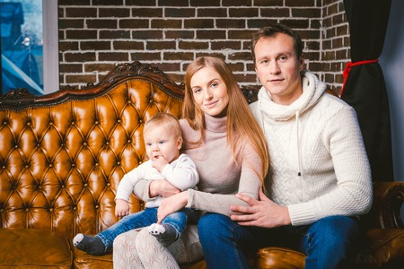 theme new year and Christmas holidays in family atmosphere. Mood celebrate Caucasian young mom dad and son 1 year old sit on a leather brown sofa at home in the living room near the Christmas tree. Imagens