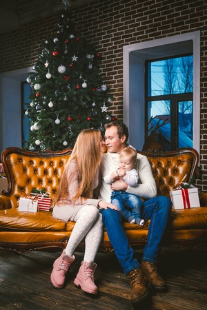 theme new year and Christmas holidays in family atmosphere. Mood celebrate Caucasian young mom dad and son 1 year old sit on a leather brown sofa at home in the living room near the Christmas tree. Banque d'images - 115268549