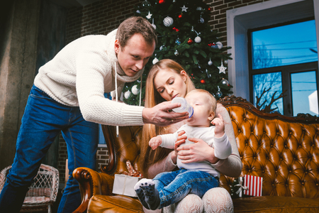 theme new year and Christmas holidays in family atmosphere. Mood celebrate caucasian young mom dad and son. The father feeds the baby from bottle. boy drinks water on couch near the Christmas tree.