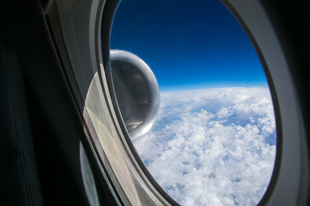 View from the window of the plane onto the wing and engines of a fokker 100 model with a blue sky and white clouds. Sunny weather.