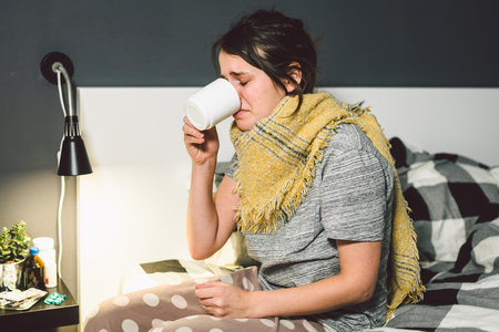 Young beautiful Caucasian woman has a cold, flu with high fever and heat at home in bed. The girl takes headache pills with a glass of water, a bitter pill is crooked. Фото со стока