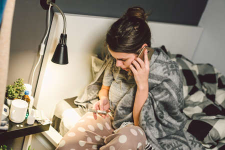 respiratory diseases and home remedies. young woman sick with cold sitting bedroom on bed holding throat sadness emotion. Sore throat man takes pills. Call phone, ask for help doctor. Call ambulance. Banque d'images