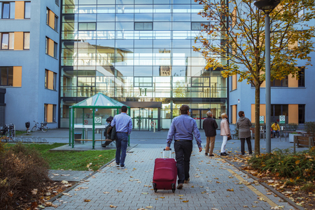 October 21, 2018. Germany, Krefeld. Entrance to Crefeld clinic in Helios, near the city of Dusseldorf. Modern European hospital. A male patient goes back with a suitcase for planned hospitalization.
