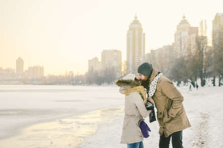 Theme love and date on nature. Young Caucasian heterosexual couple boy and girl kiss hugging warm scarf in winter near a frozen lake in winter. Bearded Man Hugging Woman. Valentine's day holiday.