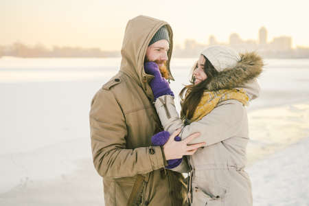 Theme love and date on nature. A young Caucasian heterosexual couple guy and girl walk in the winter along a frozen lake in winter. Bearded Man Hugging Woman. Valentine's day holiday.