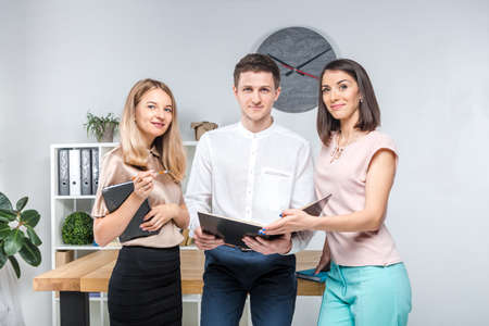 Theme business, teamwork and partnerships. A group of young people, three people, stand in an office near the table in official clothes, work with documents, make praks sign contracts.