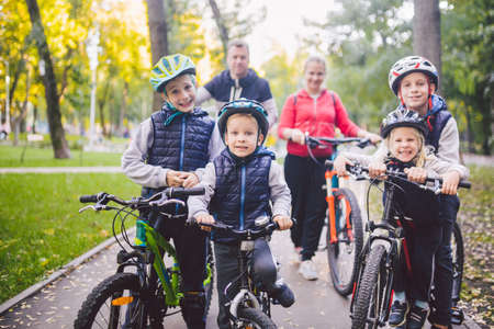 Theme family sports vacation in park in nature. big friendly Caucasian family of six people mountain bike riding in forest. Children brothers and sister stand on the background of parents in a row.