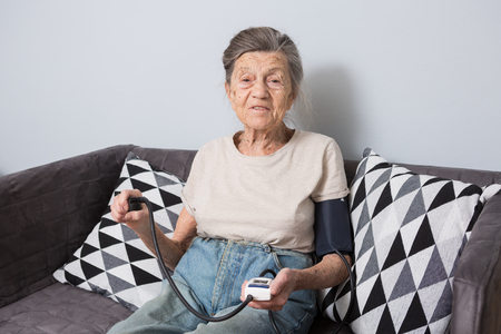 The topic is very old person and health problems. A senior Caucasian woman, 90 years old, with wrinkles and gray hair, sits home on sofa and uses blood pressure monitor to measure blood pressure.