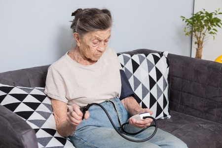 The topic is very old person and health problems. A senior Caucasian woman, 90 years old, with wrinkles and gray hair, sits home on sofa and uses a blood pressure monitor to measure blood pressure. Stock fotó
