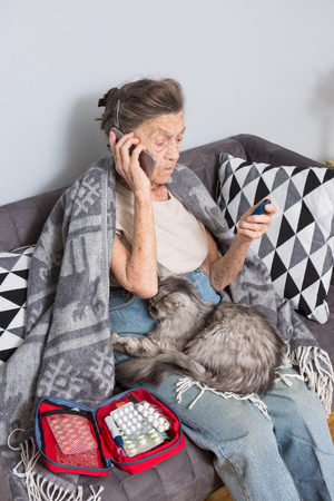 Theme old man and diabetes. older Caucasian woman with gray hair wrinkle home on sofa measures glucose level blood with help medical device using blood glucose meter. Hand ear phone call ambulance. Banque d'images - 117614364
