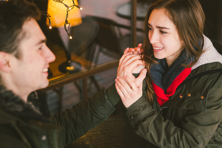 Theme love holiday Valentines Day. pair college students, Caucasian heterosexual lovers in winter, sit table of street cafe against the background window lights. Emotion romance of happiness and love.
