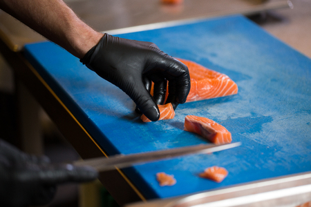 Theme cooking is a profession of cooking. Close-up of a Caucasian man's hand in a restaurant kitchen preparing red fish fillets salmon meat in black latex gloves uniform.