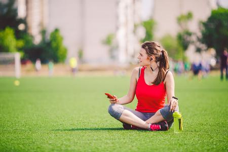 Theme sport health. beautiful young girl sitting resting on green grass. lawn stadium using technodogies. In handphone in ear headphones listens music, summer sportswear smart watch heart rate monitor