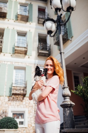 The theme is the friendship of man and animal. Beautiful young red hair Caucasian woman holding a pet dog Chihuahua breed near a house building in the summer in sunny weather.