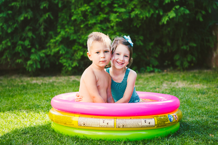 Theme is a childrens summer vacation. Two Caucasian children, brother and sister, sit in a perched round pool with water in the yard of the green grass in a bathing suit and joy happiness smile.