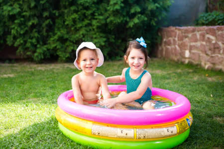 Theme is a children's summer vacation. Two Caucasian children, brother and sister, sit in a perched round pool with water in the yard of the green grass in a bathing suit and joy happiness smile.