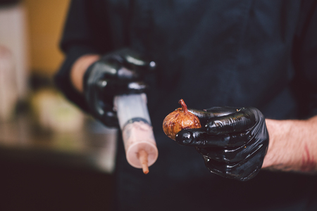 Theme cooking. Hands close up. young Caucasian man in black uniform and latex gloves in kitchen. restaurant prepares ground beef and leads into berry with syringe. Dish of figs, figs or Carian ficus.