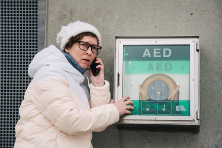 medicine cardiopulmonary resuscitation emergency call. Caucasian woman uses telephone calling 911 help. device box aed automatic defibrillator diseases, clinical death, cardiac arrest and heart attack