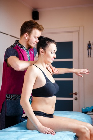 Young male massage therapist doing Relaxing massage for a girl in black underwear and dark gathered. A patient in the massage room undergoes kinesiological muscle testing, sitting on a massage table.