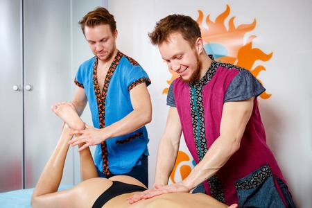 Theme medicine and rehabilitation. two twin brothers Young male doctor masseur treats massaging a young woman on a massage table private practice spa salon office posture correction.