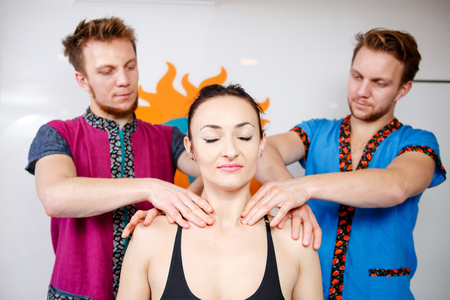 Theme medicine and rehabilitation. two twin brothers Young male doctor masseur treats massaging a young woman on a massage table private practice spa salon office posture correction. Stock Photo - 121162917