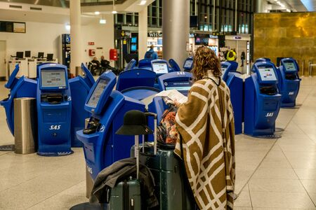 February 18, 2019. Kastrup Airport Denmark Copenhagen. Woman backs unrecognizable with large suitcases baggage independently checking in electronic ticket flight using monitor screen airport terminal. 報道画像