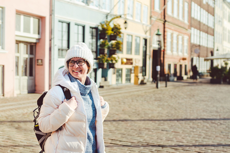 Portrait of a young Caucasian European woman tourist in glasses for the view of a white hat and a down jacket with a black backpack posing on an old Europe street in the city of Copenhagen in Denmark. Imagens