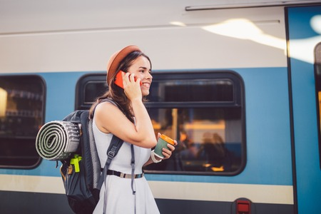 theme tourism and travel young student. beautiful young Caucasian girl in dress and hat standing at train station near train with backpack and cup coffee in hand. Uses smartphone phone technology.