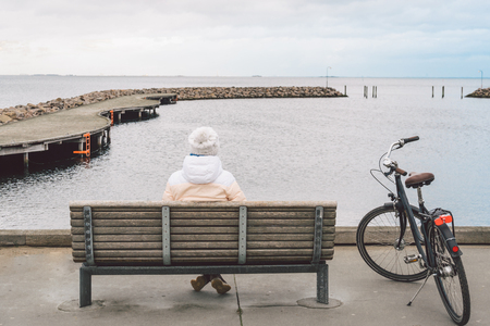 A young Caucasian woman sits with her back on a wooden bench overlooking the Baltic Sea on the seafront in Copenhagen Denmark in winter in cloudy weather. Girl walking gonoskoy bike parked nearby. Stockfoto