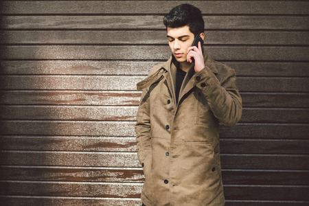 Portrait of a model young mulatto male Turkish Mediterranean race brunet in coat uses hand phone technology businessman on the street in sunny weather against the background of a wooden wall.