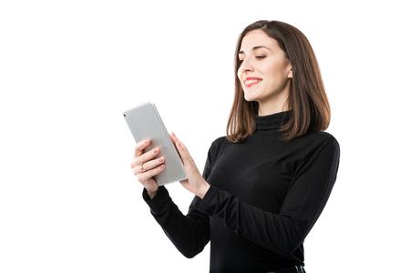 Thème de la technologie d'entreprise femme. Belle jeune femme de race blanche en chemise noire posant debout avec les mains de la tablette sur fond blanc isolat. Profession Marketeur Ventes Publicité sur les réseaux sociaux. Banque d'images