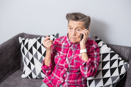 An old elderly woman grandmother with gray hair sits at home on the couch using the hand phone, a telephone conversation to hear the bad news. Emotion fear scare.