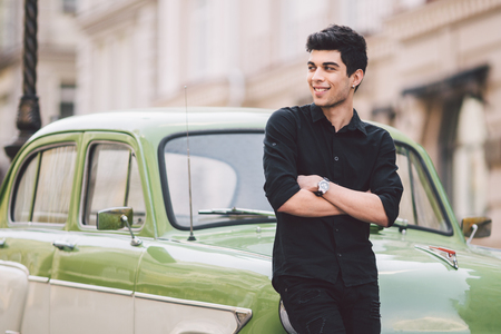 portrait, handsome, male, model, brunette Mediterranean race Turkish man stands near a retro car of green color posing in a black shirt and jeans in the city. Banque d'images