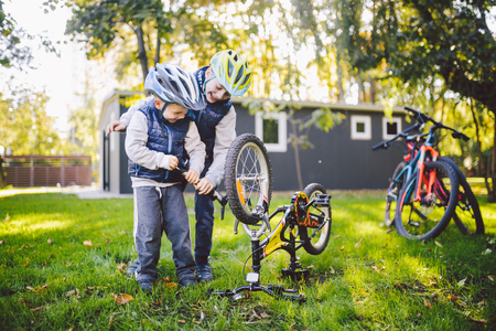 Two children, older boys and younger brother learning repair bike. Two guys siblings in helmets and single clothes use pump tool and pump air into bicycle wheel in park background of the house.