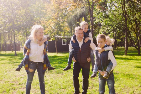 Theme family active leisure outside in nature. large Caucasian family with four children. Mom and Dad actively relaxing. enjoy life in park near house on grass. Children on back shoulders roll on top.