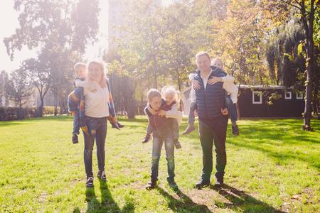 Tema de ocio activo familiar al aire libre en la naturaleza. numerosa familia caucásica con cuatro hijos. Mamá y papá se relajan activamente. disfruta de la vida en el parque cerca de la casa en el césped. Los niños sobre los hombros traseros se enrollan hacia arriba.