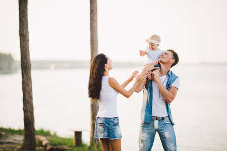 family outdoor recreation with sea views. young Caucasian family with one year old child in arms, stylish denim clothes resting, spending day off, tourism holidays, high point of cliff see sea horizon