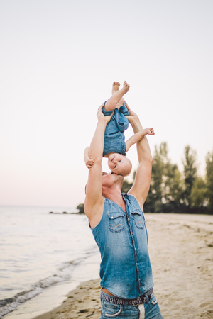 Theme Fatherhood and rest with a child at sea. Young handsome Caucasian father plays plays enjoys throwing up in arms his child up in summer daughter on the sandy beach on the seashore. 写真素材