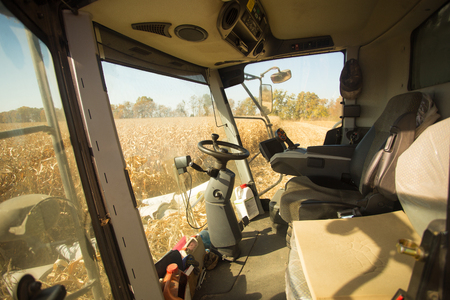View of the field of corn from the cab of a combine harvester on a sunny day. Workplace of a combine operator. Theme is agricultural and agriculture. Banco de Imagens