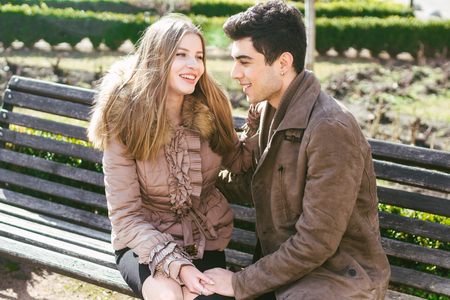 Young multiracial couple, male and female heterosexual students in love. A date in a city park on a wooden bench. Young brunette man with dark skin and a Caucasian woman in an embrace on a sunny day.