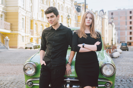 Young multiracial couple, male and female lovers heterosexual people students. Beautiful models posing standing near a retro car in the city. Dressed in black clothes.