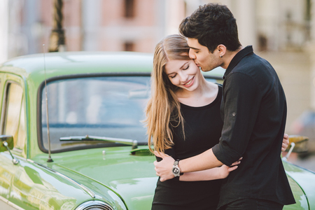 Young multiracial couple, male and female lovers people students. Beautiful models posing standing near a retro car in the city. Dressed in black clothes.